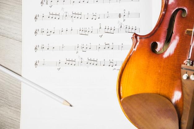 Crayon et violon sur la note de musique sur la table Photo gratuit
