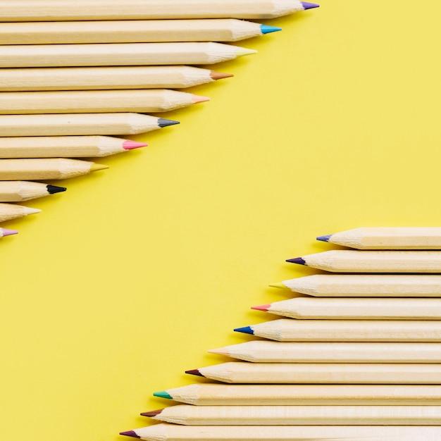 Crayons de bois colorés dans une rangée sur fond jaune Photo gratuit