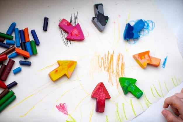 Crayons de cire faits maison à partir de l'épave de vieux crayons en les faisant fondre au four à haute température sous forme de silicone. crayons de couleur sous la forme de flèches se trouvent sur le papier, enfant de la main Photo Premium