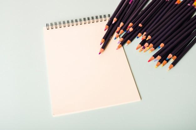 Crayons colorés et bloc-notes blanc spirale blanche sur fond blanc Photo gratuit