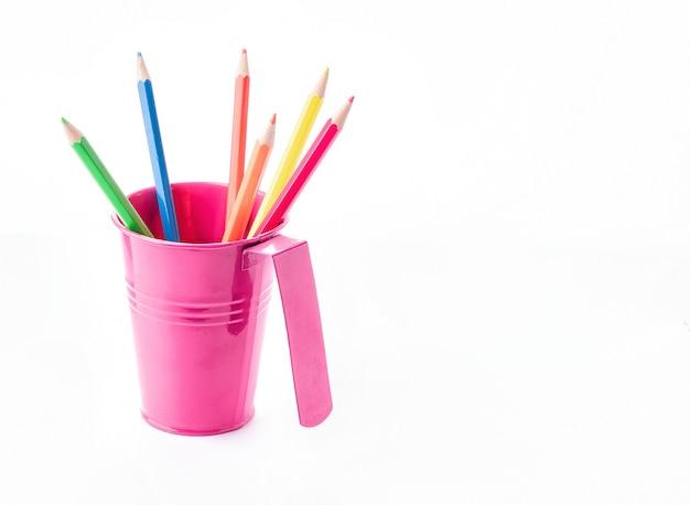 Crayons colorés dans un seau isolé sur blanc. idée créative pour le dessin et le style. Photo Premium