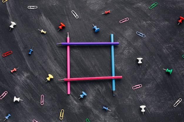 Crayons colorés en forme de carré sur fond sombre Photo gratuit