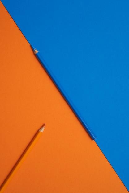 Crayons De Couleur Bleu Et Orange Isolés Sur Une Table Orange Et Bleue Photo Premium
