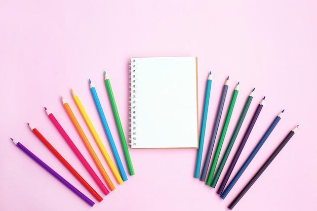 Crayons De Couleur Et Cahier Sur Mur Clair. Photo Premium