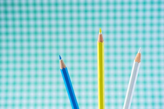 Crayons de couleur sur fond pastel dans une cage avec un espace pour le texte. Photo Premium