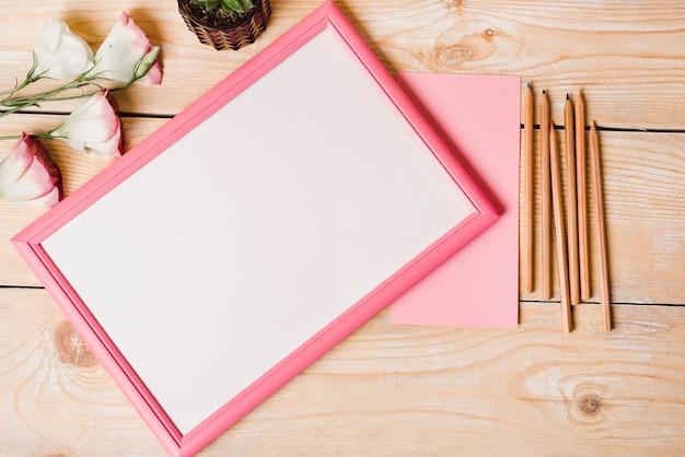 Crayons de couleur; papier; fleurs eustoma et cadre photo blanc avec bordure rose sur une table en bois Photo gratuit