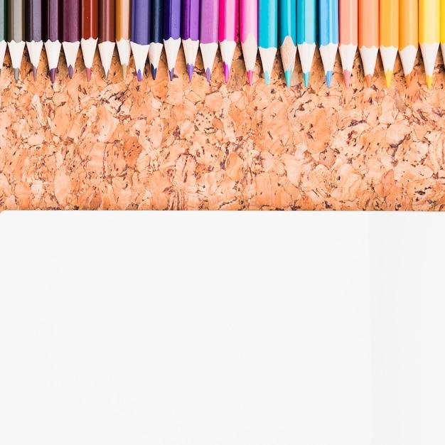 Crayons de couleur placés au-dessus d'une feuille de papier sur un fond de liège Photo gratuit