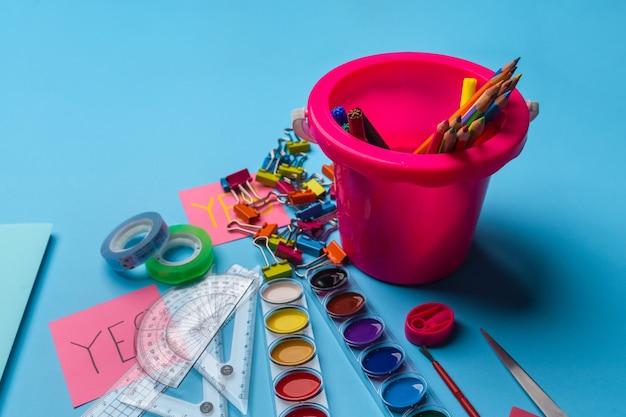 Des crayons de couleurs vives et des feutres dans un seau rose à côté desquels se trouvent des peintures Photo Premium