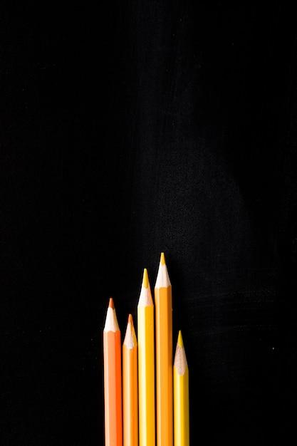 Crayons jaunes sur le bureau noir Photo gratuit