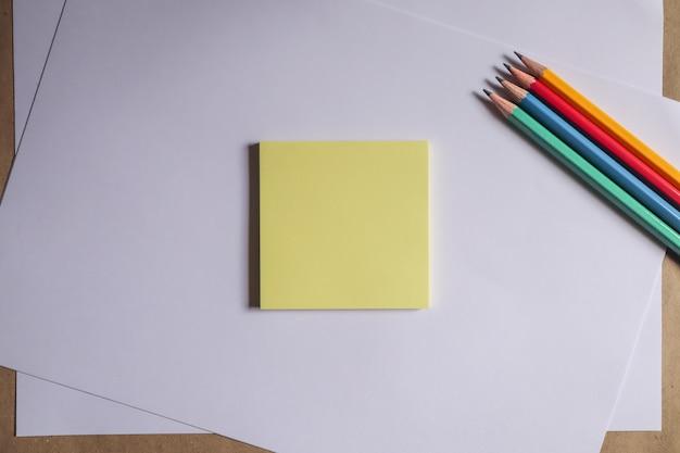 Crayons multicolores et cahiers marron sur fond blanc Photo Premium