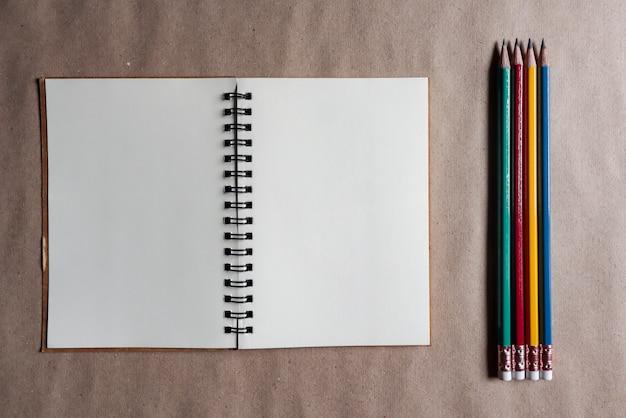 Crayons multicolores avec des notes marron sur papier brun Photo Premium
