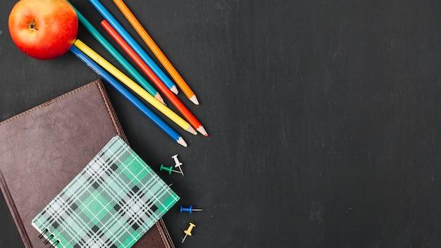 Crayons multicolores près de cahier Photo gratuit
