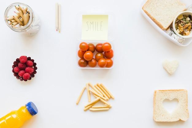 Crayons et note collante près de la nourriture assortie Photo gratuit