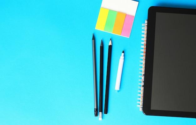 Crayons, papier à lettres et tablett sur fond bleu et retour au concept de l'école. Photo Premium
