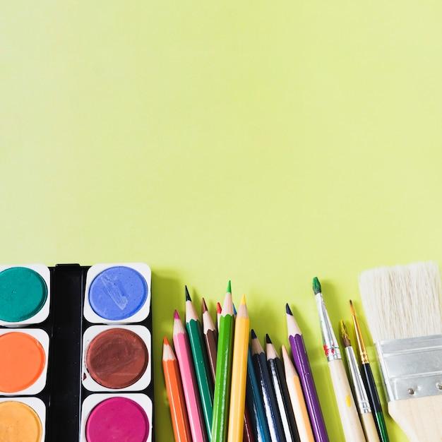 Crayons et pinceaux près de l'aquarelle Photo gratuit