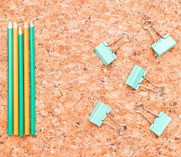 Crayons et pinces-notes sur le bureau Photo gratuit
