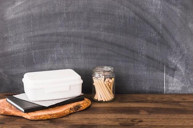 Crayons près de la boîte à lunch en plastique et cahier Photo gratuit