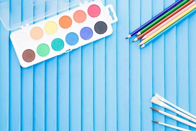 Crayons près des pinceaux et aquarelle Photo gratuit