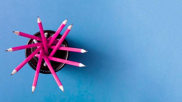 Crayons roses dans le support sur fond bleu Photo gratuit