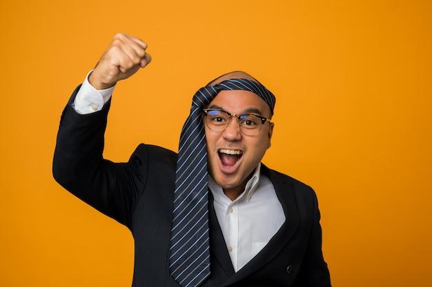 Crazy Business Homme Chauve Gueule De Bois Portant Une Cravate Sur La Tête Lever Son Poing Sur Jaune Photo Premium