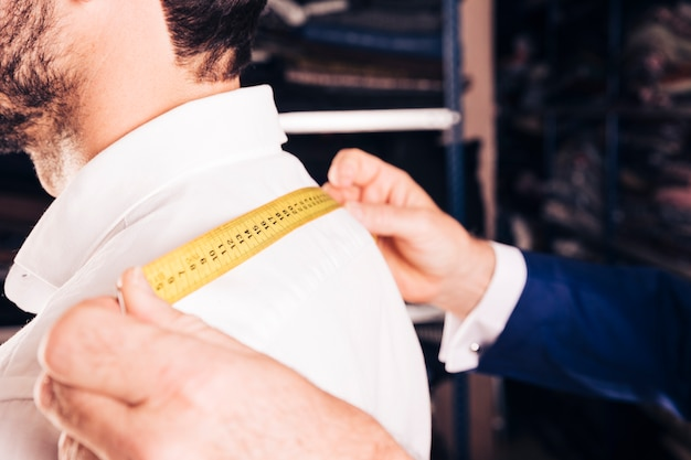 Créateur de mode prenant la mesure du dos de son client avec un ruban à mesurer jaune Photo gratuit