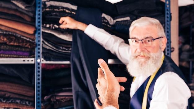 Un créateur de mode prenant un tissu sur une étagère pour son client Photo gratuit