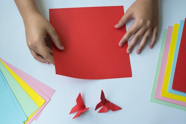 Création d'origami un papillon. les mains des enfants font un papillon origami. Photo Premium