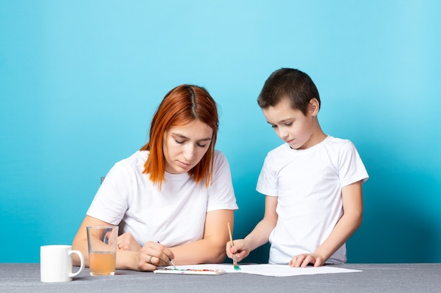 La Créativité Des Enfants. Mère Et Fils Peignent Avec De La Peinture Sur Fond Bleu Photo Premium