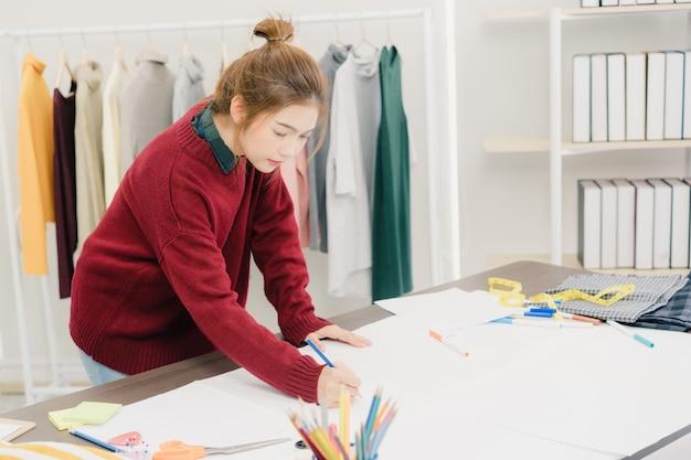 Créatrice de mode féminine asiatique belle professionnelle travaillant avec des croquis de tissu Photo gratuit