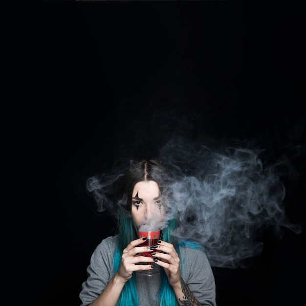 Creepy girl avec verre à vin rouge fumé Photo gratuit