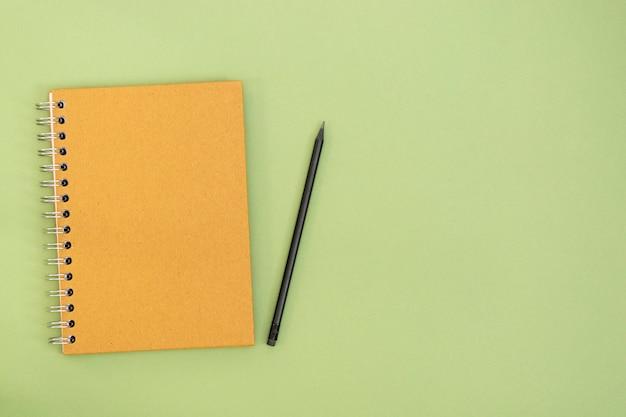 Créez Un Cahier Fermé Et Un Crayon Sur Fond Vert Avec Espace De Copie. Espace De Travail, Entreprise Ou éducation Moderne Et Minimaliste. Photo Premium