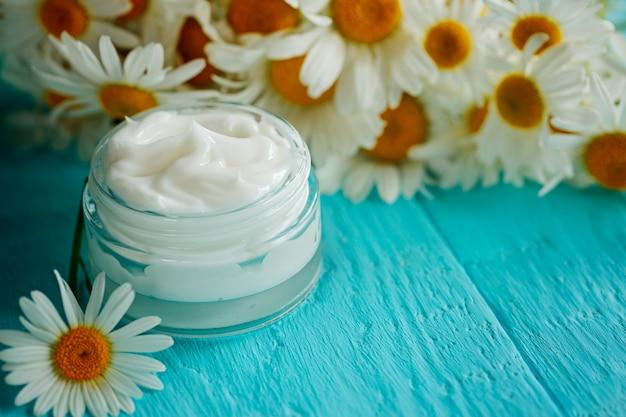 Crème cosmétique à la fleur de camomille ou un corps et un visage sur une table en bois bleue Photo Premium