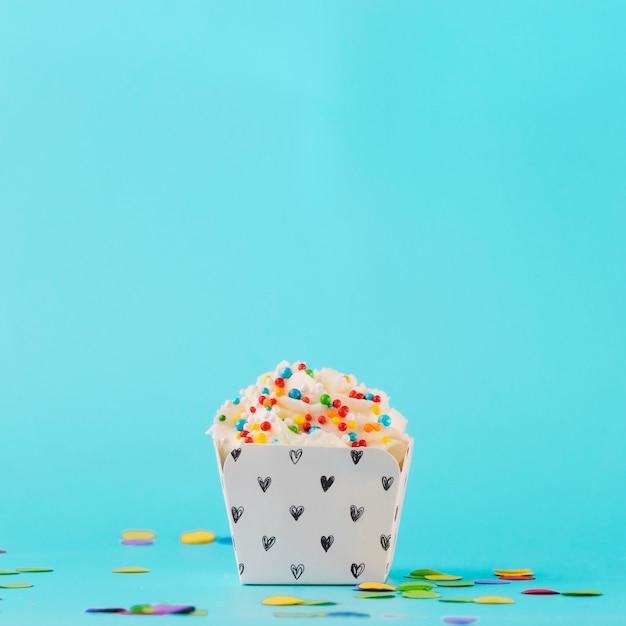 Crème fouettée blanche avec pépites colorées et confettis sur fond bleu Photo gratuit