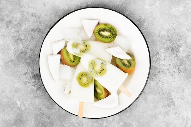 Crème glacée au yaourt / lait de coco de kiwi sur fond clair Photo Premium