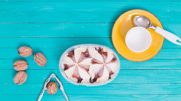 Crème glacée dans un bol en plastique et une assiette jaune avec une tasse et une cuillère et des noix avec des noix Photo gratuit