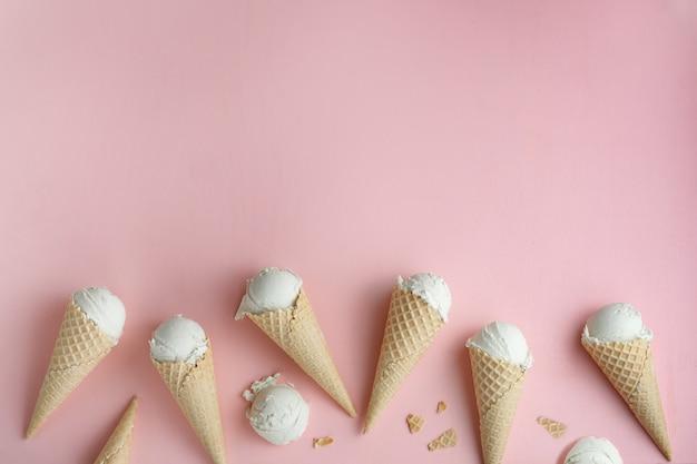 Crème glacée faite maison dans des cônes de gaufres sur fond rose. copyspace pour un texte Photo Premium