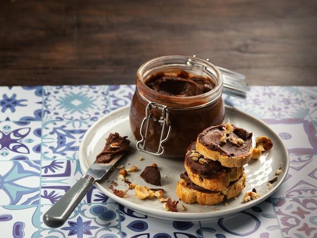 Crème De Noisettes Dans Un Bol Avec Des Noisettes Et Des Tranches De Pain Grillé Avec De La Crème Au Chocolat. Photo Premium