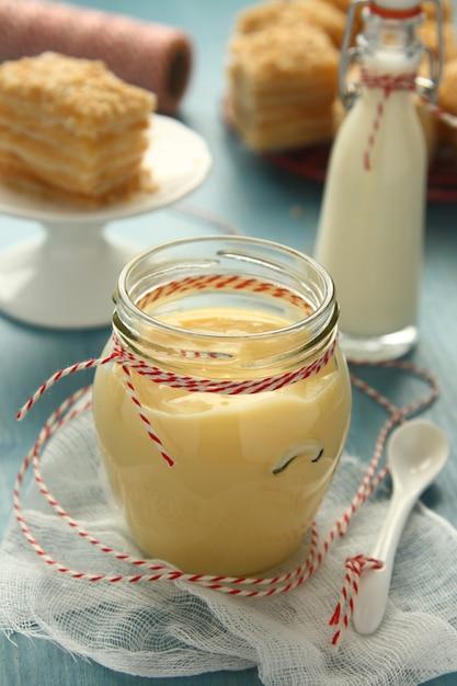 Crème pâtissière en pot de verre sur un fond en bois bleu Photo Premium