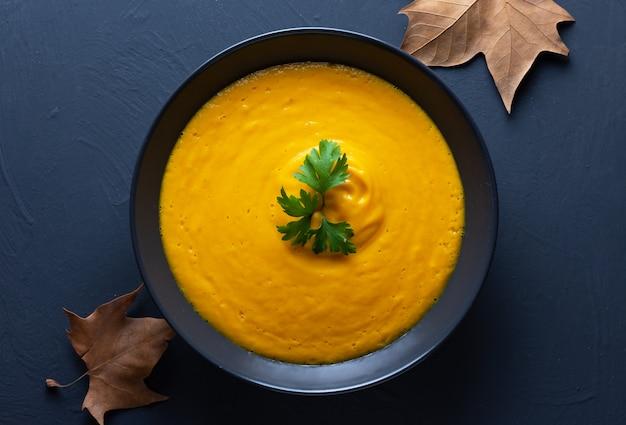 Crème de potiron servie sur une plaque noire sur un fond sombre avec des feuilles d'automne Photo Premium
