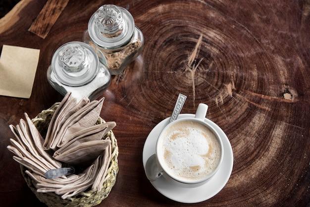 Crème pour café ou thé avec une tasse de café et une tasse de thé avec du papier de soie et du sucre sur la table en bois Photo Premium