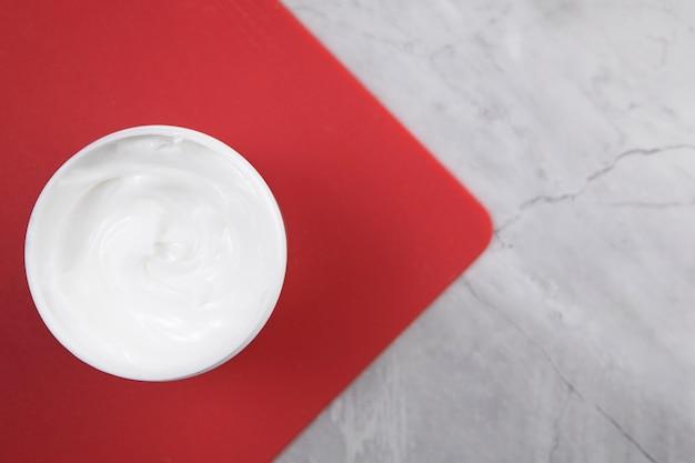 Crème pour le corps à plat sur un tableau rouge Photo gratuit