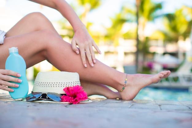Crème solaire, chapeau, lunettes de soleil, fleur et jambes de femme bronzées près de la piscine Photo Premium