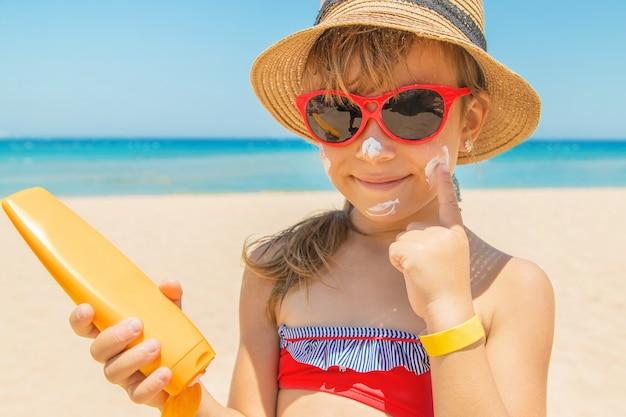 Crème solaire sur la peau d'un enfant Photo Premium