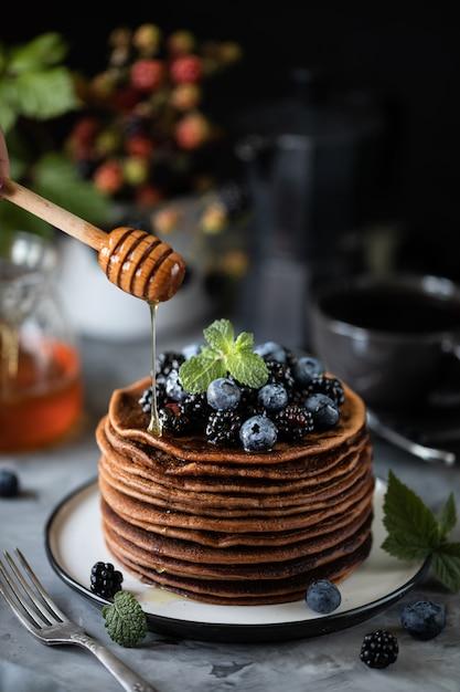Crêpe Au Chocolat Avec Des Baies Et Des Fruits Avec Du Miel, Avec Du Sucre En Poudre Volant Et Un Bouquet De Fleurs Sauvages Sur La Table. Foncé Photo Premium