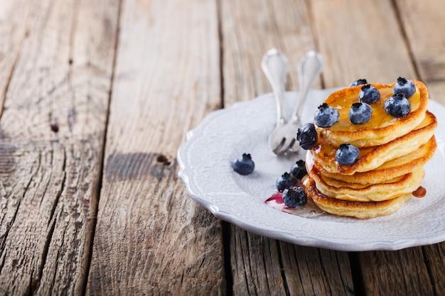 Crêpe pliée pile de miel liquide et bleuets frais Photo Premium