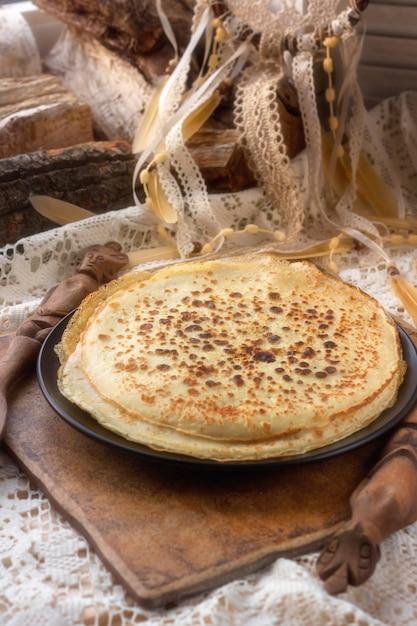 Crêpes sur une assiette. la table rustique est recouverte d'une nappe blanche tricotée. gamme de couleurs claires. souvenirs d'enfance Photo Premium