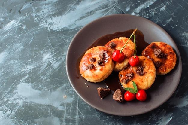 Crêpes au fromage cottage avec des cerises et du chocolat sur une table en béton fond noir. Photo Premium