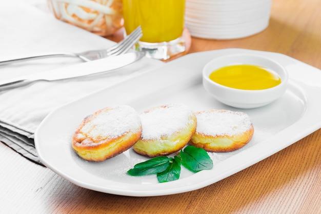 Crêpes au fromage cottage avec du sucre en poudre se bouchent Photo Premium