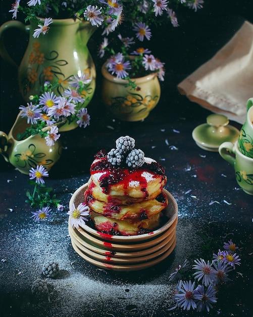 Crêpes au fromage cottage, syrniki, beignets de lait caillé aux baies congelées (blackberry) et sucre en poudre dans une assiette vintage. petit déjeuner gastronomique Photo gratuit