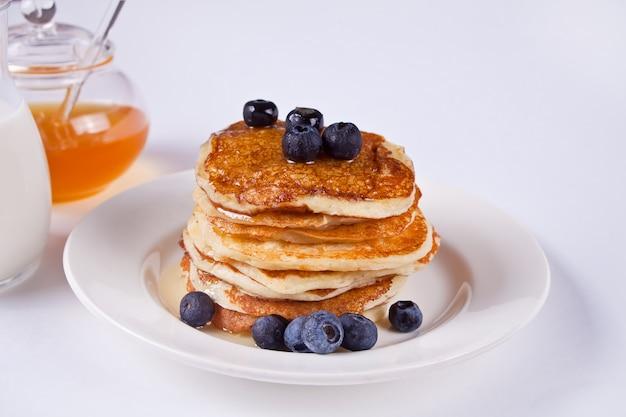 Crêpes aux baies et au miel sur fond blanc Photo Premium